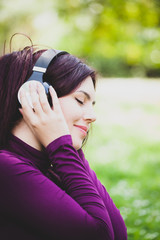 Woman in park listening music with headphones.