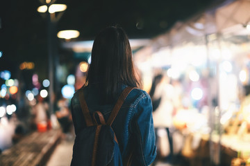 Young traveller woman walking on city street at night. Fotomurales