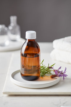 Brown glass bottle with lavender flower on plate.