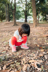 Asian little girl playing with a magnifying glass