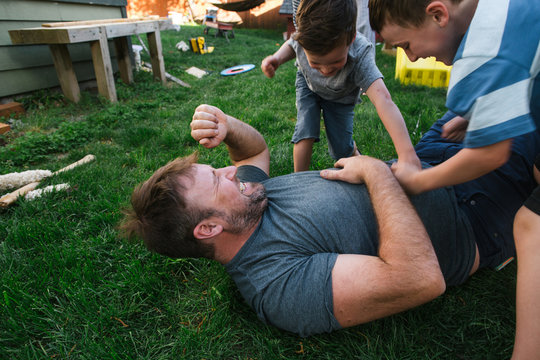 Dad playing with kids in backyard