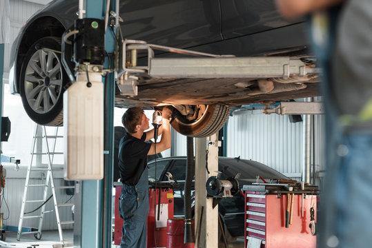 Garage worker repairing car from below