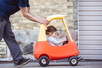 Portrait of a toddler girl being pushed by her daddy in a outdoor toy car