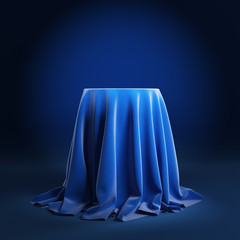 Round podium covered with blue cloth on a blue background.