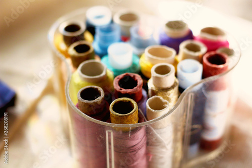 colored threads in transparent plastic sewing box on fabric canvas