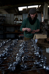 Blacksmith putting iron roses in rows in his workshop.