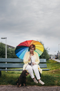Senior woman sitting on a park bench with her puppy dog and holding a colorful umbrella