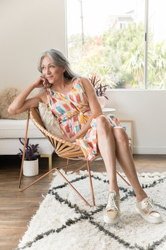 Smiling mature woman sitting on chair at home