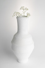 Still life composition of white pottery vase and small white flowers on white background