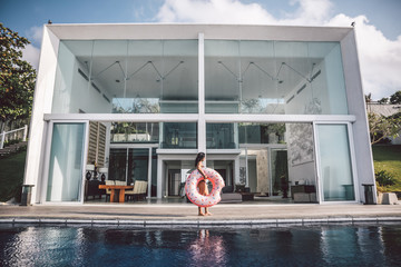 beautiful woman with inflatable pink donut in front of luxury villa