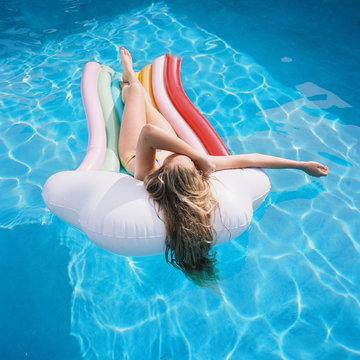 kids on rainbow floaty in blue pool on film