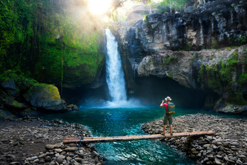 Travel photographer with backpack and camera in hand make epic photo amazing waterfall in the sun rays on background nature landscape Fototapete