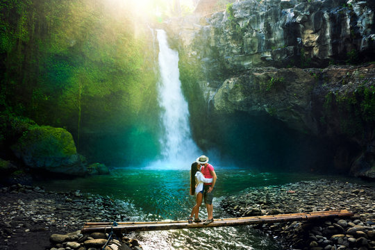 Young couple enjoy honeymoon vacation on tropical island Bali, hugs and kisses on background scenery waterfall Tegenungan and amazing nature landscape at sunrise