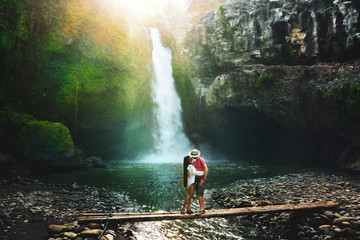 Active lifestyle couple travel in Asia and explore amazing waterfall hidden in tropical rainforest jungle Fototapete