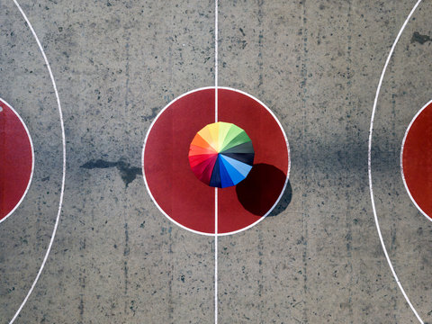 Overhead view of person with colorful umbrella on basketball court