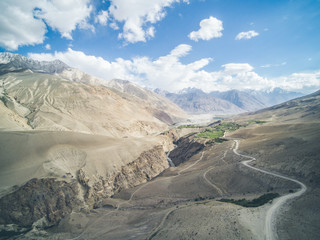 dirt road leading through the pamir range with the himalay in the back