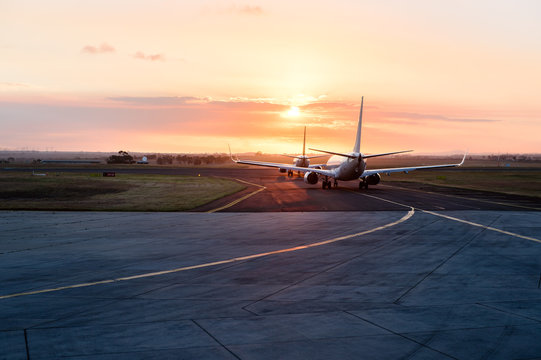 Two aircraft lined up awaiting to enter runway at sunset