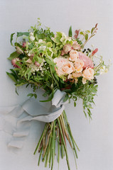 Overgrown wildflower bouquet with grey silk ribbon against a grey linen backdrop