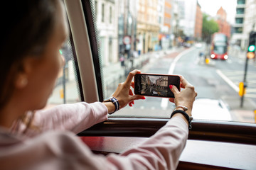 Girl taking photo from the second deck of a double-decker in London