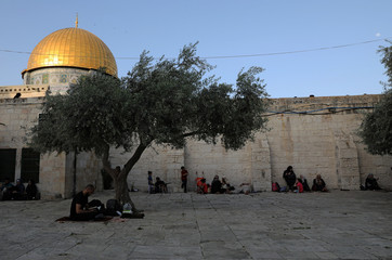 A Palestinian man reads the Koran outside the al-Aqsa mosque, on the compound known to Muslims as al-Haram al-Sharif and to Jews as Temple Mount, during the holy month of Ramadan in Jerusalem's Old City