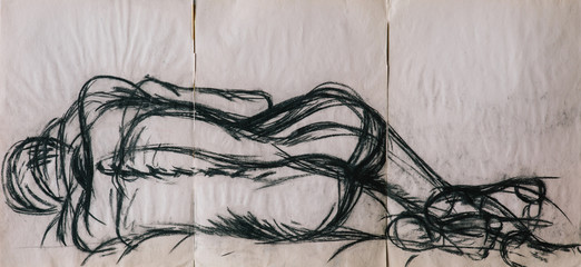Charcoal life drawing of a woman lying naked in a bed