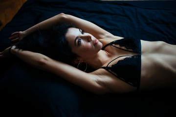woman lying on the bed stretching out her arms