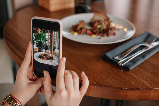 Crop female's hands with phone taking picture of plate with food