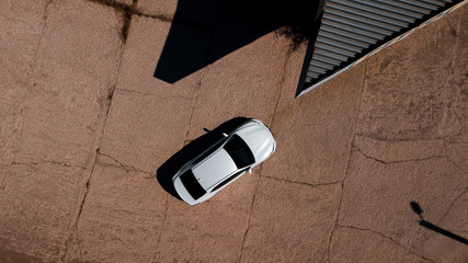 aerial view of a brand new car near an abandoned petrol station in the desert