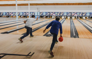 Man and older woman and  throwing bowling balls at same time..