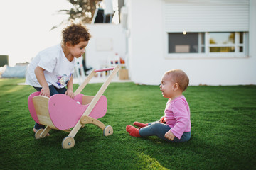 Siblings fighting over doll stroller in yard