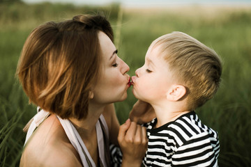 Mother kiss her little son outdoor
