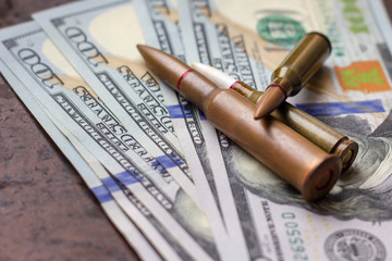 Weapon bullets on American dollars background. Military industry, global arms trade and crime concept