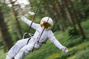 Astronaut enjoying merry go round carousel in park