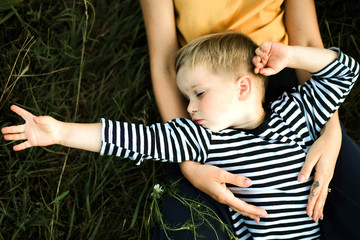 Portrait of a mother and boy lying outdoor.