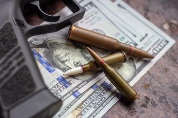 Weapon bullets and black gun on American dollars background. Military industry, war, global arms trade and crime concept