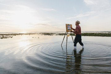 En plein air painter painting in sea with easel