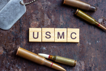 USMC sign with weapon bullets and army dog tags on rusty metal background. Military industry, United States Marine Corps concept