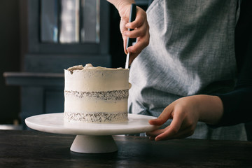 Midsection of woman decorating layered cake with icing cream