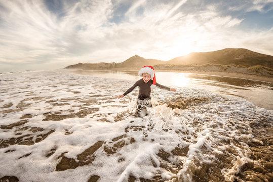 Smiling boy wearing Santa hat playing in water on beach