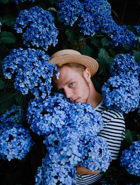Young man standing amidst lilac hydrangea flowers