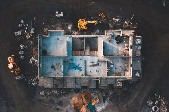 Aerial birds eye image of the frame of a house being built on a construction site at sunset - Wooden floor and walls are visible
