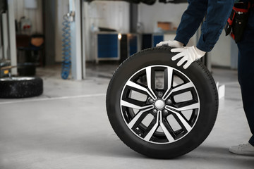 Technician rolling car wheel in automobile repair shop closeup. Space for text