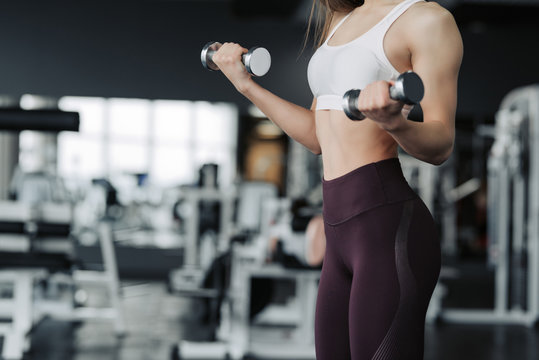 Cropped body close up of young attractive woman in sport clothes holding weight dumbbell doing fitness workout in the gym.