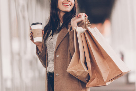 Beautiful fashionable woman with shopping bags and coffee walking near mall.