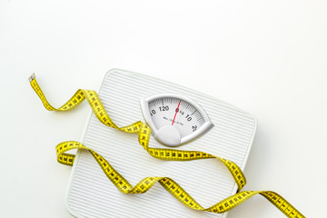 bathroom scales and measuring tape for weight loss concept on white background top view Fotobehang