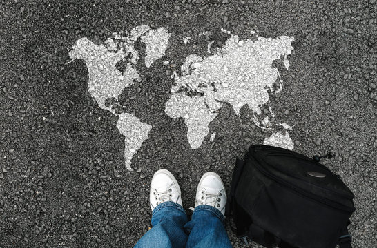 World map on an asphalt road an man in shoes