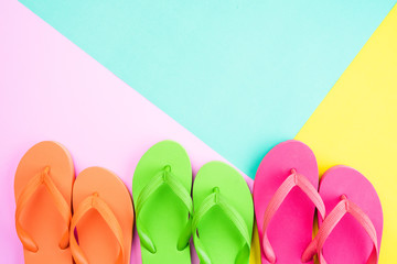 Top view of colorful flip flop on pink and yellow background for summer holiday and vacation concept.