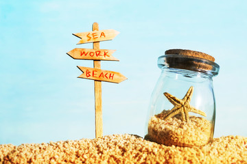 Vacation background with starfish in a glass vessel and a wooden pointer with the text Sea, Work, Beach against the sea, soft focus