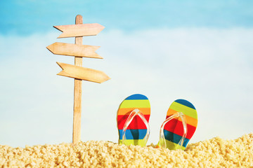 Vacation background with flip flops and wooden signpost with space for your text against the sea, soft focus