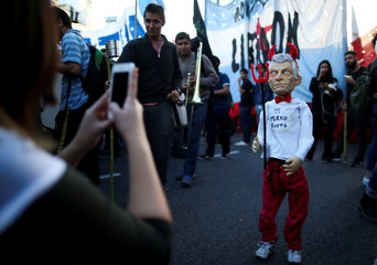 A student takes a picture of a puppet depicting Argentina's President Mauricio Macri as the devil during a protest demanding better salaries for the teachers and against cutbacks in university budgets in Buenos Aires